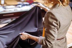Female fashion designer working on suiting fabric with dressmaking accessories on table stock photo