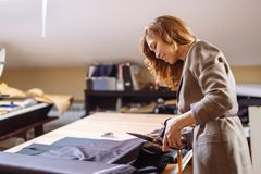 Female fashion designer working on suiting fabric with dressmaking accessories on table royalty free stock photography