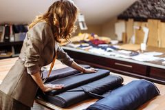 Female fashion designer working on suiting fabric with dressmaking accessories on table royalty free stock image