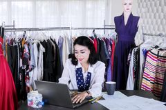 Female fashion designer works with a laptop. Picture of female fashion designer working with a laptop while sitting in the workplace royalty free stock photo