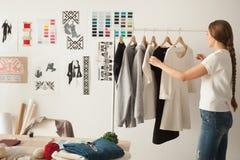 Female fashion designer working on new womenswear collection in. Female fashion designer works on new womenswear collection for clients in cozy workshop studio Stock Image