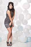 Female fashion model posing with a balloon backgro. Caucasian female posing in a grey cocktail dress in front of a white and blue balloon wall Stock Photography
