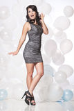 Female fashion model posing with a balloon background. Caucasian female posing in a grey cocktail dress in front of a white and blue balloon wall Royalty Free Stock Photos