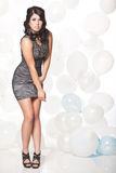 Female fashion model posing with a balloon background. Caucasian female posing in a grey cocktail dress in front of a white and blue balloon wall Royalty Free Stock Photo