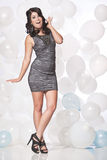 Female fashion model posing with a balloon background with a fun. Caucasian female posing in a grey cocktail dress in front of a white and blue balloon wall Stock Photography