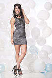 Female fashion model posing with a balloon background with a hap. Caucasian female posing in a grey cocktail dress in front of a white and blue balloon wall Stock Photos