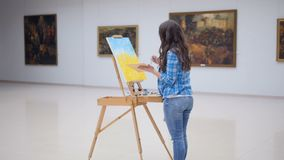 Female fashion painter drawing a picture on easel.. Female painter drawing a picture on easel stock video