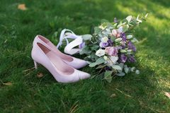 Female fashion pink wedding shoes with elegant bride`s bouquet in pastel tones on green grass background. Stock Photo