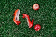 Female fashion red wedding shoes and two red garnets on green grass background.  Royalty Free Stock Photos