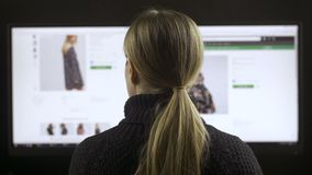 Female fashion shopping online on wide screen pc. Back view of female sitting at wide screen computer and fashion shopping online. Woman searching clothing stock video