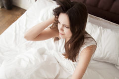 Female feeling exhausted after sleepless night. Tired sleepy woman with messy hair sitting in bed after wake up in the morning. Young female feeling exhausted Royalty Free Stock Images