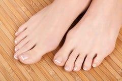 Female feet. Well-groomed female feet on wooden floor stock photos
