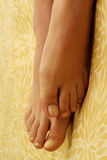 Female feet. On a yellow print blanket royalty free stock images