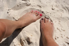 Female Feet. Two different female feet in the white sand Stock Images