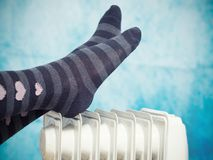 Female feet above the heater. Heating in cold weather royalty free stock image