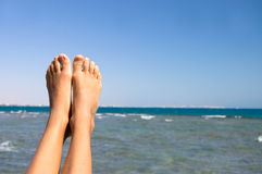 Female feet against the sea Stock Photography