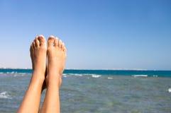 Female feet against the sea stock photography