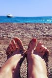 Female feet against the sea. Female feet with adherent small pebbles on the background of the sea Royalty Free Stock Images