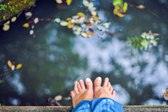 Female feet on the background of the pond Stock Photo