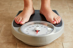 Female feet on a bathroom scale Stock Photo