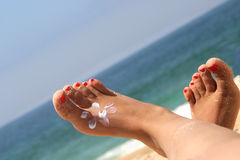 Female feet on the beach. Female feet with sun pictured by sun protect cream Royalty Free Stock Photography