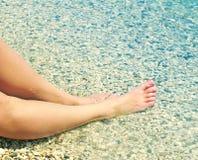 Female feet on a beach against the sea in a summer sunny day. Stock Photos