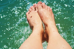 Female feet on a beach against the sea in a summer sunny day. Royalty Free Stock Image