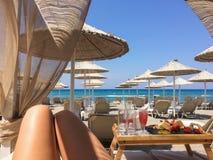 Female feet on the beach background with deckchairs Stock Photos