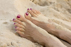 Female feet on the beach covered in sand Stock Photo