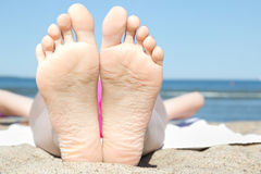 Female feet on the beach near the sea Royalty Free Stock Images