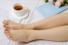 Female feet in bed book tea flowers royalty free stock photo