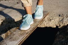 Female feet in beige pants and sneakers are on the board Stock Photo