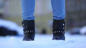 Female feet in black leather winter shoes in snow. Close up of female feet in winter boots standing in the snow. Feet of woman in black winter shoes shifting stock footage