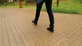 Female feet in black shoes and jeans are on the road stock video