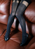 Female feet in black stockings on a leather Royalty Free Stock Photos