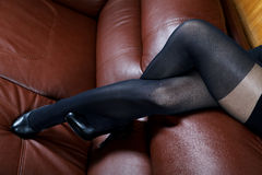 Female feet in black stockings on a  sofa Royalty Free Stock Images