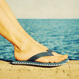 Female feet in blue flip-flops, retro image Royalty Free Stock Photography