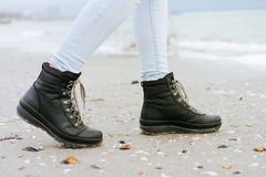 Female feet in blue jeans and black winter boots are on the beackground. Female feet in blue jeans and black winter boots are on the beach sand Stock Image