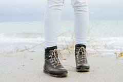 Female feet in blue jeans and black winter boots standing on the beach Royalty Free Stock Photography