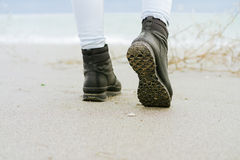 Female feet in blue jeans and black winter boots standing on the beach. Against the sea Royalty Free Stock Image