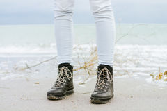 Female feet in blue jeans and black winter boots standing in the sand. Against the sea Stock Photo