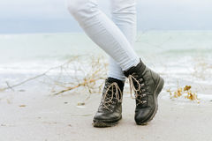 Female feet in blue jeans and black winter boots standing in the. Sand at the beach Stock Images