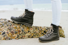 Female feet in blue jeans and black winter boots standing. On a stone against the sea Royalty Free Stock Photo