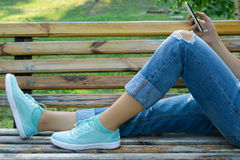 Female feet in blue jeans and a mobile phone in hand close-up Stock Photos