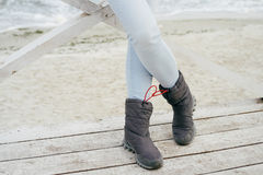 Female feet in blue jeans and sporting boots standing. On a wooden platform on the beach in autumn Stock Photo