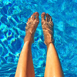 Female feet in blue water Stock Photos