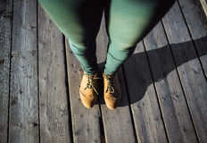 Female feet in brown boots and green pants standing on wood background. Walking fashion hiking concept. Female feet in brown boots and green pants on wood Royalty Free Stock Images
