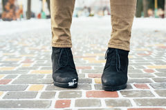 Female feet in brown jeans and black winter boots standing on a Royalty Free Stock Photography