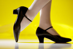 Female feet in character shoes. Yellow background, character shoes on woman Royalty Free Stock Photography