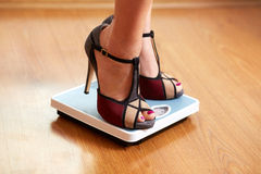 Female feet in color stilettos with weight scale Royalty Free Stock Photo